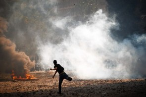 A protester in Cairo throws a rock at police as demonstrations over a video insulting the Prophet Muhammad continued. Egypt's president criticized the use of violence in the protests.