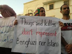 "A Libyan woman holds a sign that reads ""Thugs and killers don't represent Benghazi nor Islam"""